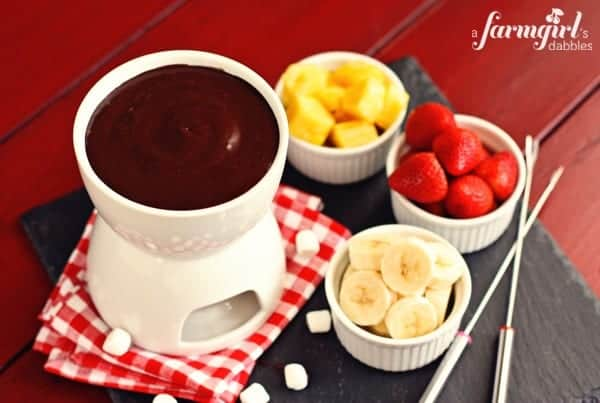 a pot of chocolate marshmallow fondue with cups of fruit
