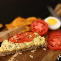 a piece of bread topped with herby egg salad and tomatoes