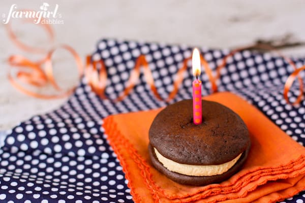 a whoopie pie with a pink candle on top