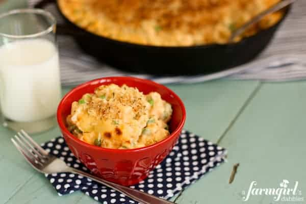 Red bowl filled with macaroni and cheese with peas