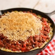 a skillet pan of Spaghetti Hotdish topped with Garlic Bread Crumbs