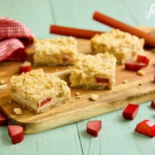 Square Rhubarb Cream Cheese Bars on a wooden cutting board with fresh rhubarb