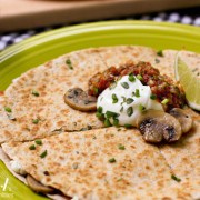 A round quesadilla on a plate topped with sliced sauteed mushrooms, sour cream, salsa, scallions and a lime wedge