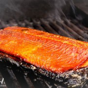 A browned side of salmon cooking on a grill