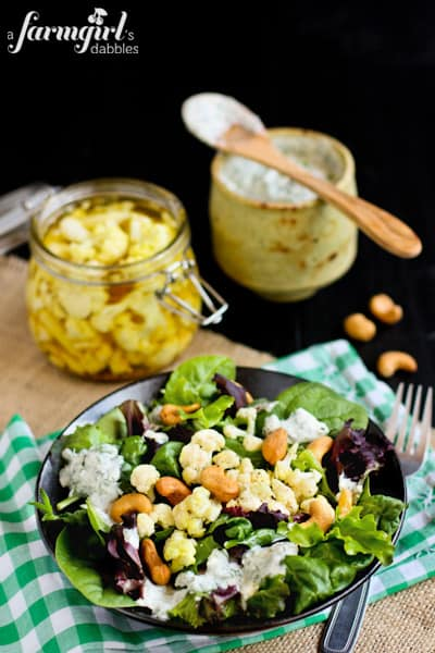 fresh salad, a jar of pickled cauliflower, and summer dressing