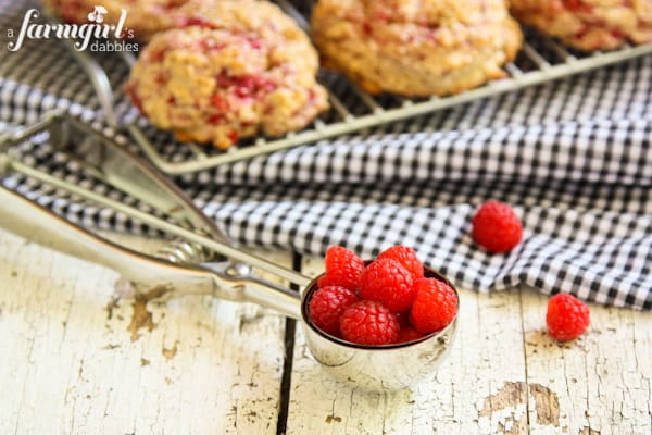a cookie scoop of raspberries and a pan of scones