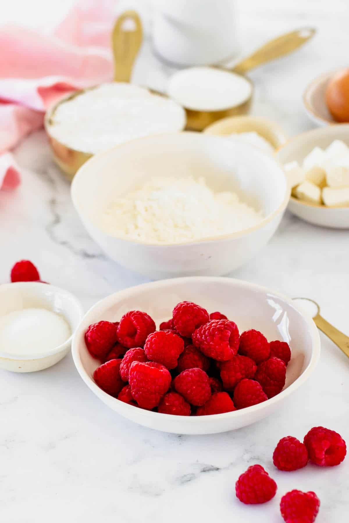 A white bowl of raspberries and a white bowl of flour