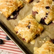 Square blueberry hand pies with glaze on a parchment-lined baking sheet