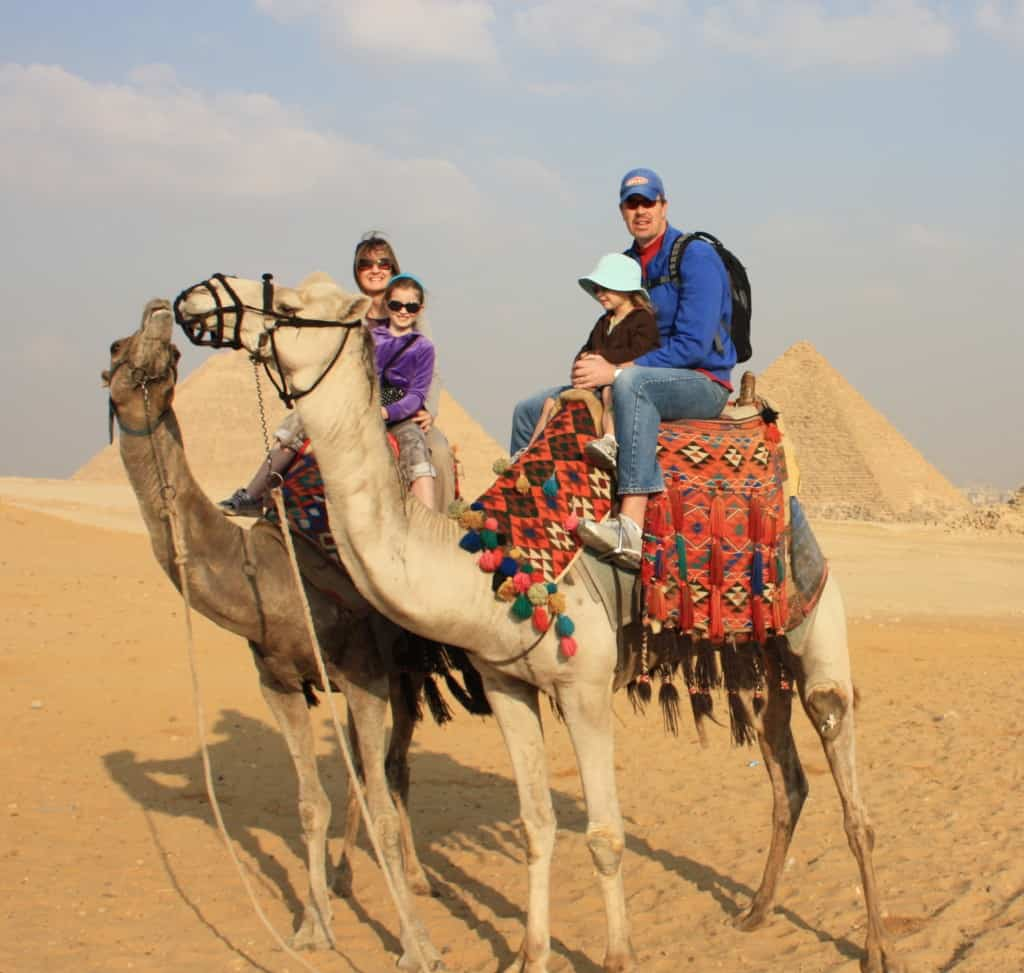 a family riding camels in Egypt