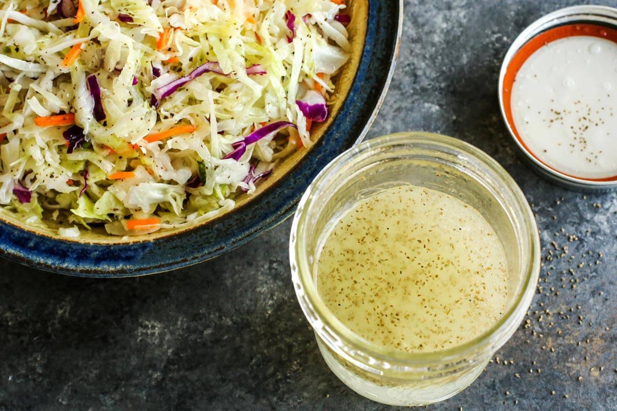 a jar of vinegar coleslaw dressing and a bowl of coleslaw salad