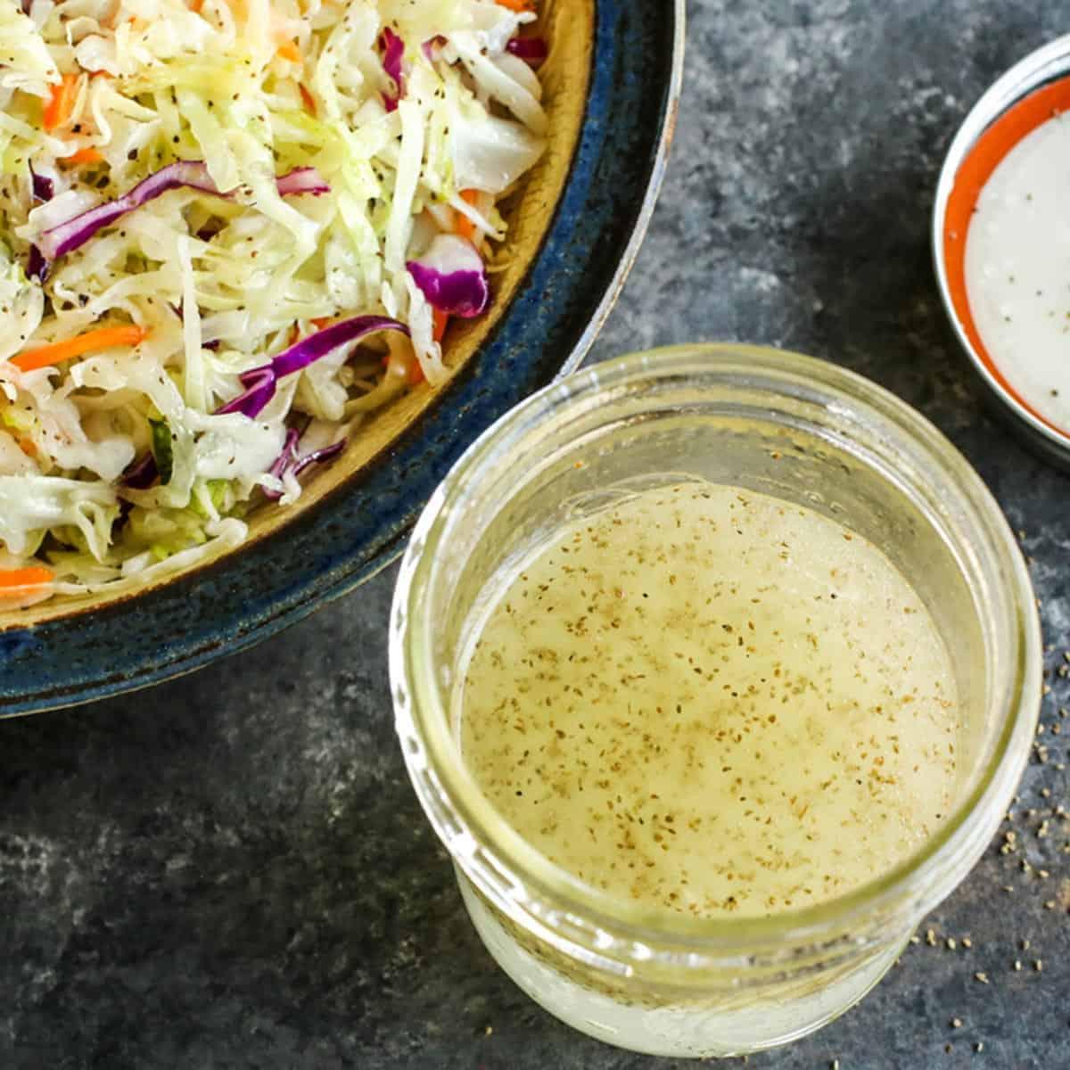 a jar of vinegar coleslaw dressing and a bowl of shredded cabbage