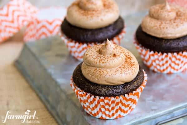 Chocolate Cupcakes in orange paper wrappers topped with buttercream