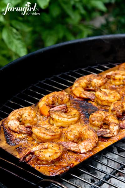 shrimp on a plank grilling on a charcoal grill