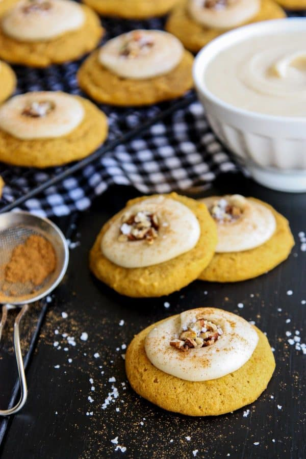 Melt-In-Your-Mouth Pumpkin Cookies with a bowl of frosting