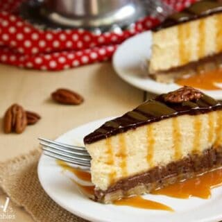 two slices of Turtle Pecan Cluster Cheesecake drizzled with caramel