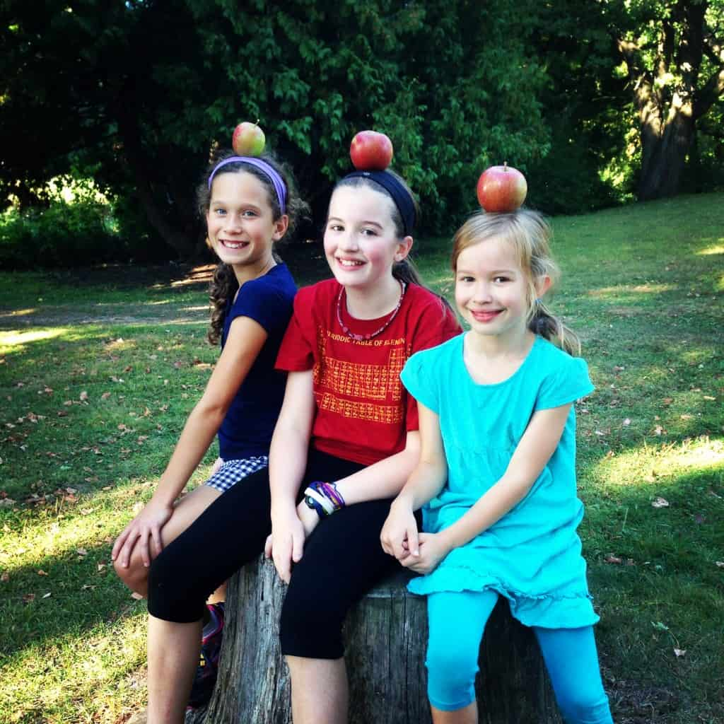 three girls posing with apples on their heads