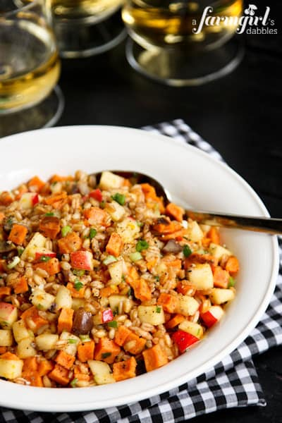a bowl of Farro and Spiced Honey Salad with three glasses of white wine