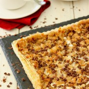 Caramel Tart topped with Almonds, Coconut, and Marshmallows on a black serving board