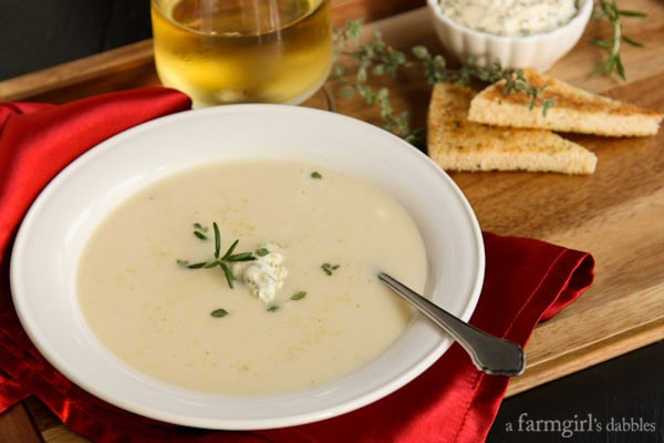 a bowl of Potato Soup with a dish of Herby Compound Butter