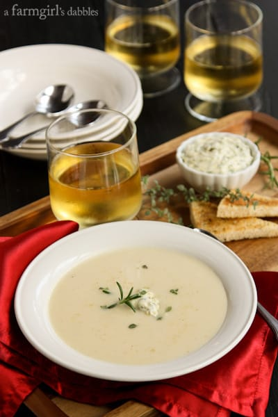 a bowl of Potato Soup with glasses of white wine