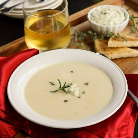 A white bowl of creamy potato soup topped with fresh herb compound butter