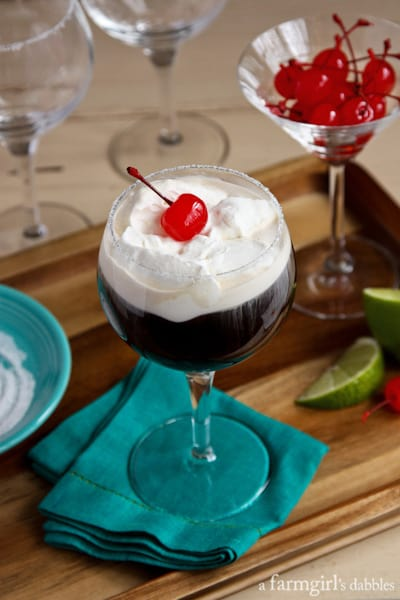 Mexican Coffee in a tall, stemmed glass with whipped cream and cherries