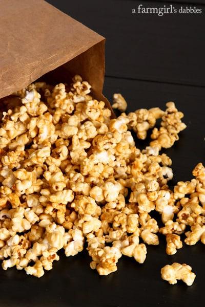 Caramel Popcorn spilling out of a brown paper bag