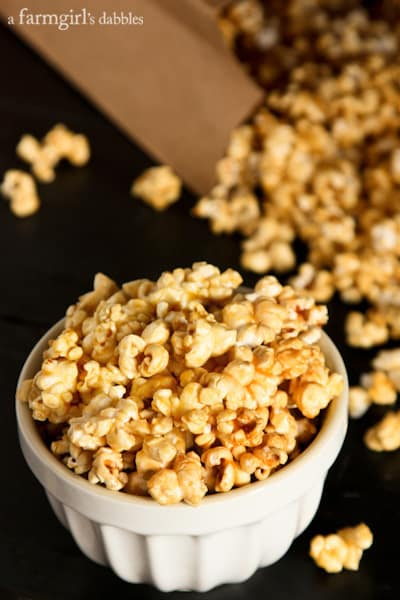 Caramel Popcorn in a white bowl and a paper bag