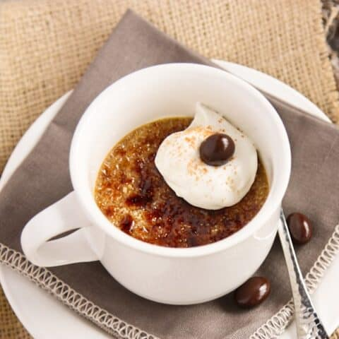 A white mug of creme brulee with whipped cream and a chocolate covered espresso bean