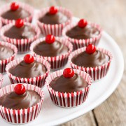 Striped baking cups filled with chocolate and topped with a red round candy