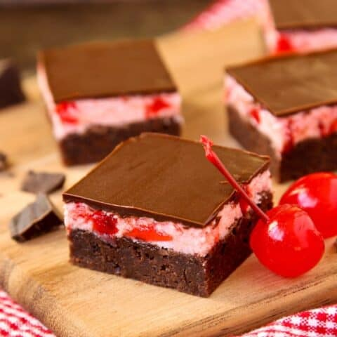 Brownie squares with cherry frosting and chocolate glaze on a wooden board