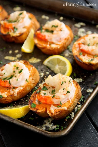 toasts topped with shrimp on a rimmed baking pan