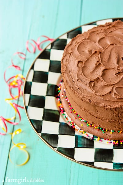 a chocolate cake on a checkered cake stand