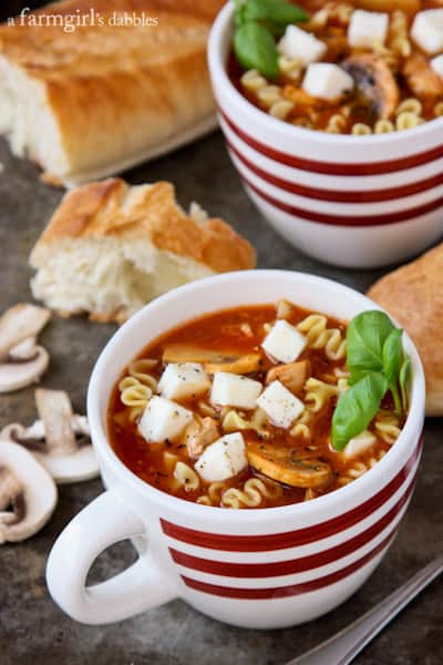 two mugs of Lasagna Soup with a loaf of bread and sliced mushrooms