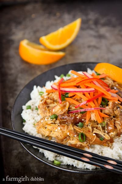 a bowl of rice topped with Orange Chicken and Fresh Asian Slaw