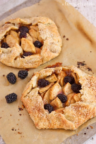 Two Apple and Blackberry Tarts on a Parchment Lined Baking Sheet