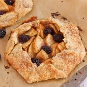 A rustic Apple Blackberry Tart on parchment paper