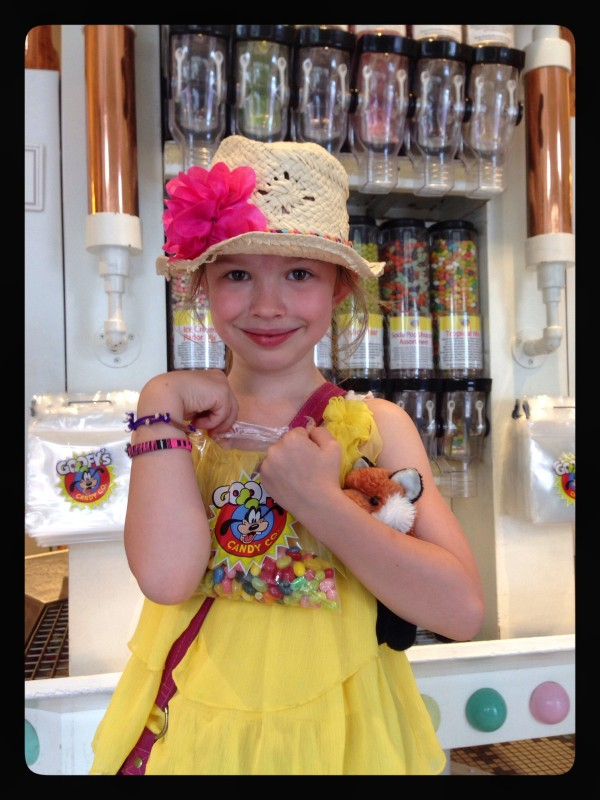 a young girl in a yellow dress at a candy store