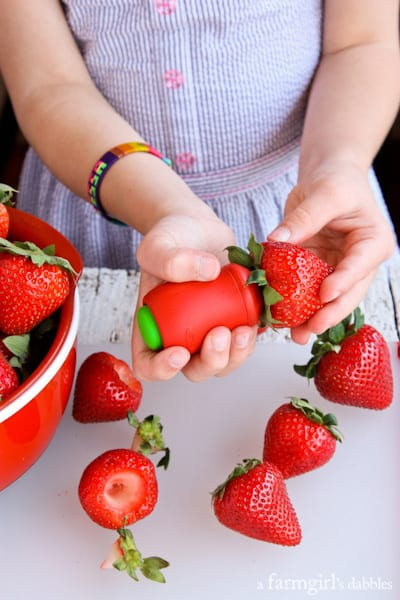 a young girl hulling strawberries
