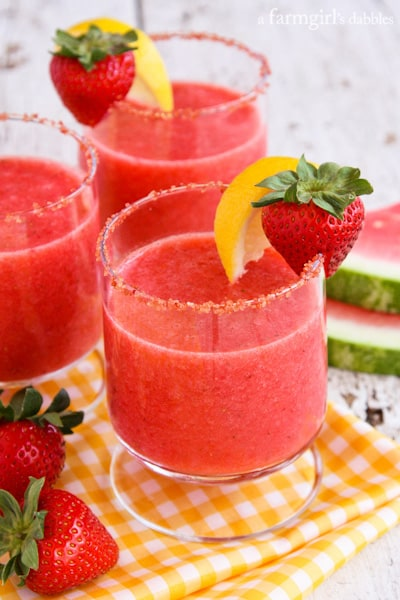 Frozen Strawberry Watermelon Lemonade in cocktail glasses with strawberry sugar on the rims
