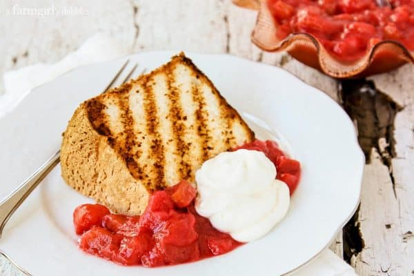 slice of grilled cake on a white plate with a bowl of rhubarb sauce