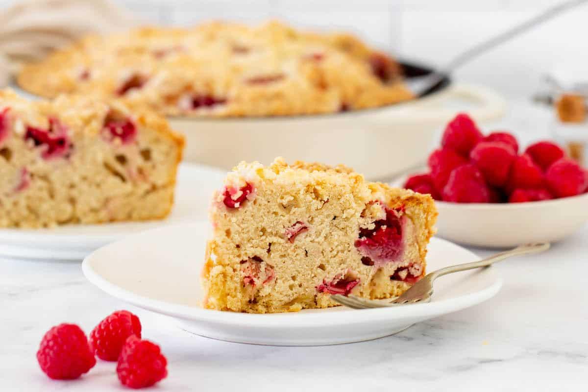 Two slices of raspberry rhubarb coffee cake on white plates