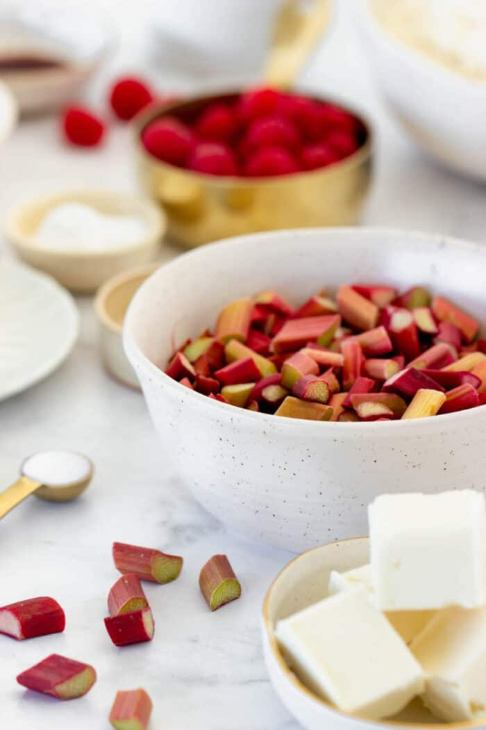 A bowl of chopped rhubarb with cubed butter and raspberries in the background
