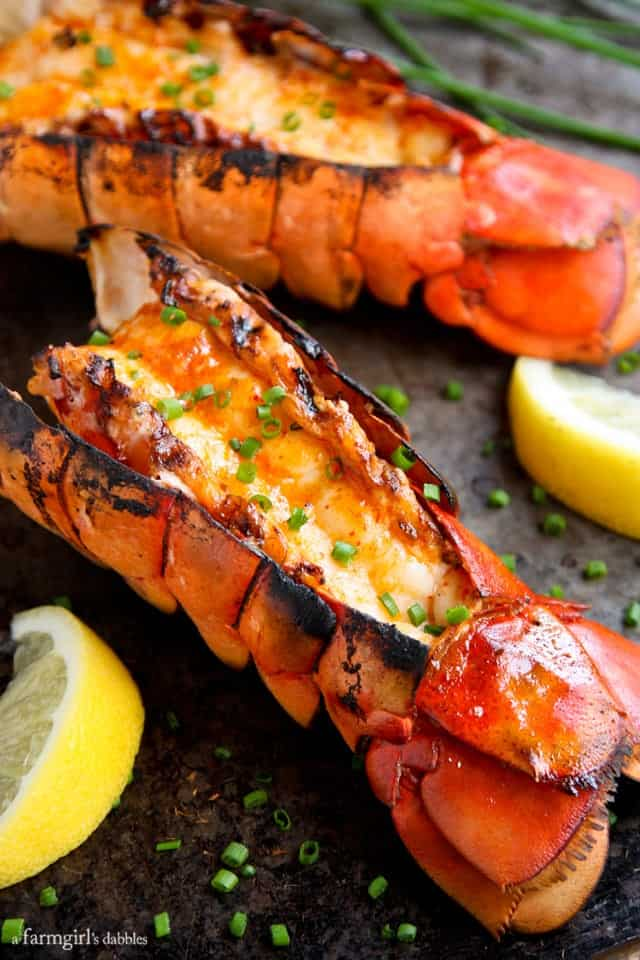 Grilled Lobster Tails with Sriracha Butter - on Black Platter with lemon slices