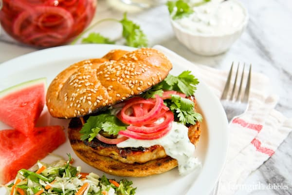 Grilled Honey Sriracha Chicken Burgers with Cilantro Cream and Pickled Onions - afarmgirlsdabbles.com #chicken #grilling #sriracha