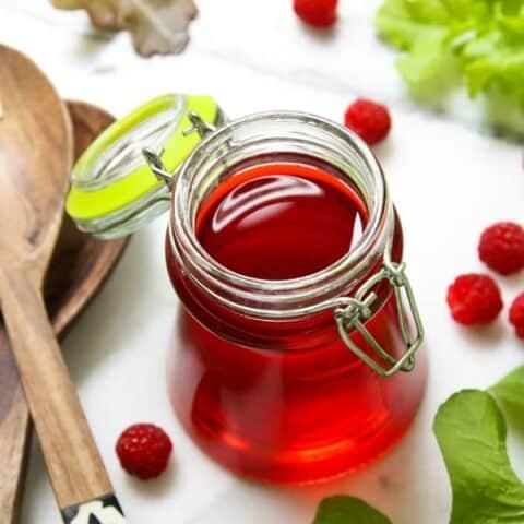 a clear jar of raspberry vinegar