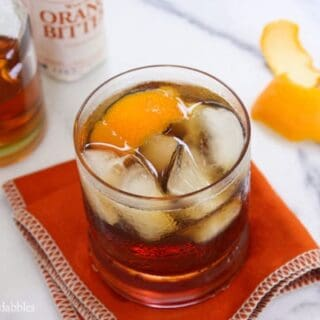 A Glass of Old Fashioned Bacon Bourbon on the Rocks Next to an Orange Peel