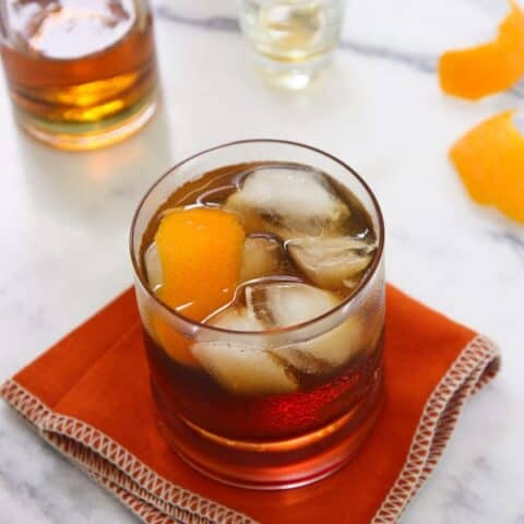 A rocks glass of Bacon Bourbon Old Fashioned with ice and orange peel