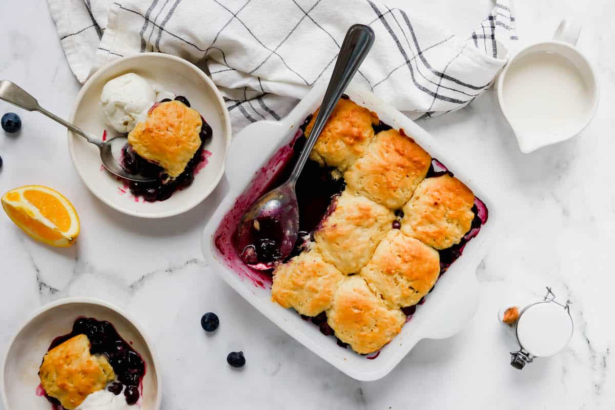 A baking dish of blueberry cobbler with three pieces missing