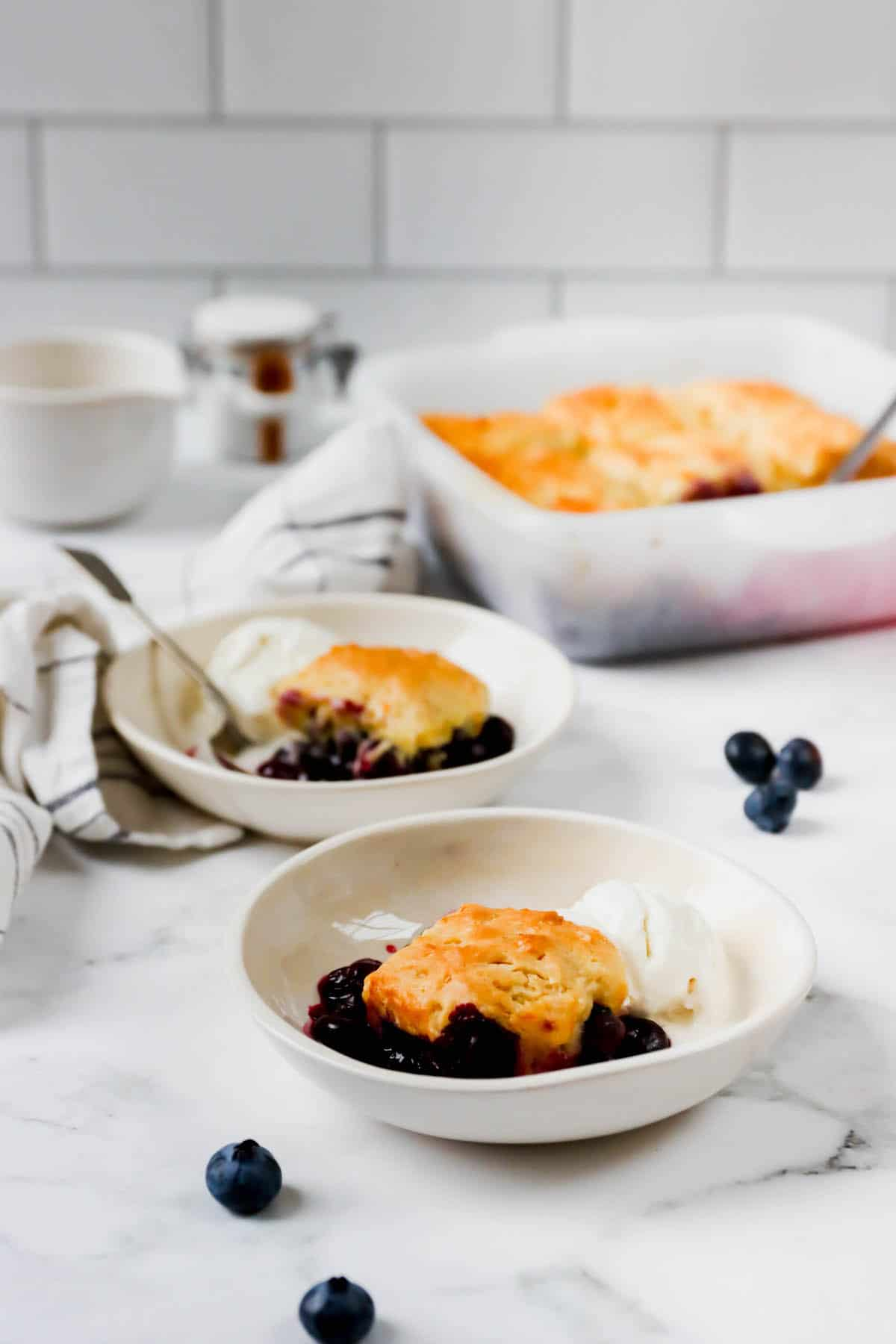 Two plates with blueberry cobbler and the baking dish in back